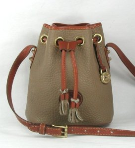 "A taupe and British Tan Dooney & Bourke AWL Drawstring showing ""grommets"""